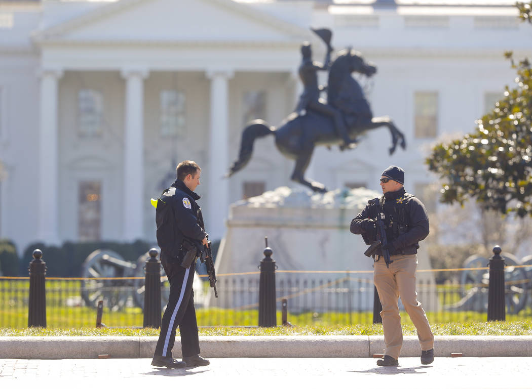 Law enforcement officers at Lafayette Park across from the White House in Washington, close the area to pedestrian traffic, Saturday, March 3, 2018. A man apparently shot himself along the north f ...