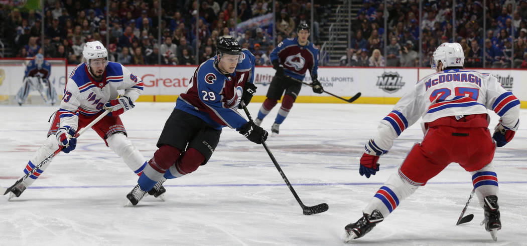 Colorado Avalanche center Nathan MacKinnon (29) carries the puck against New York Rangers center Mika Zibanejad (93) and Rangers defenseman Ryan McDonagh (27) in the third period of an NHL hockey  ...