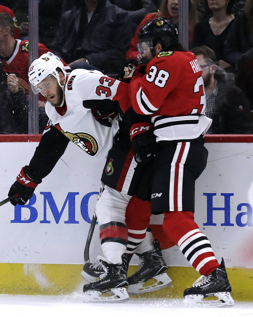 Ottawa Senators defenseman Fredrik Claesson, left, is checked by Chicago Blackhawks left wing Ryan Hartman during the second period of an NHL hockey game Wednesday, Feb. 21, 2018, in Chicago. (AP  ...