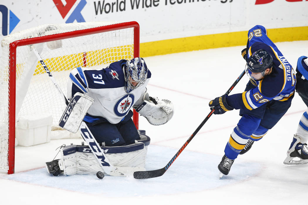 Winnipeg Jets goaltender Connor Hellebuyck blocks a shot by St. Louis Blues' Paul Stastny, right, during the third period of an NHL hockey game Friday, Feb. 23, 2018, in St. Louis. The Jets won 4- ...