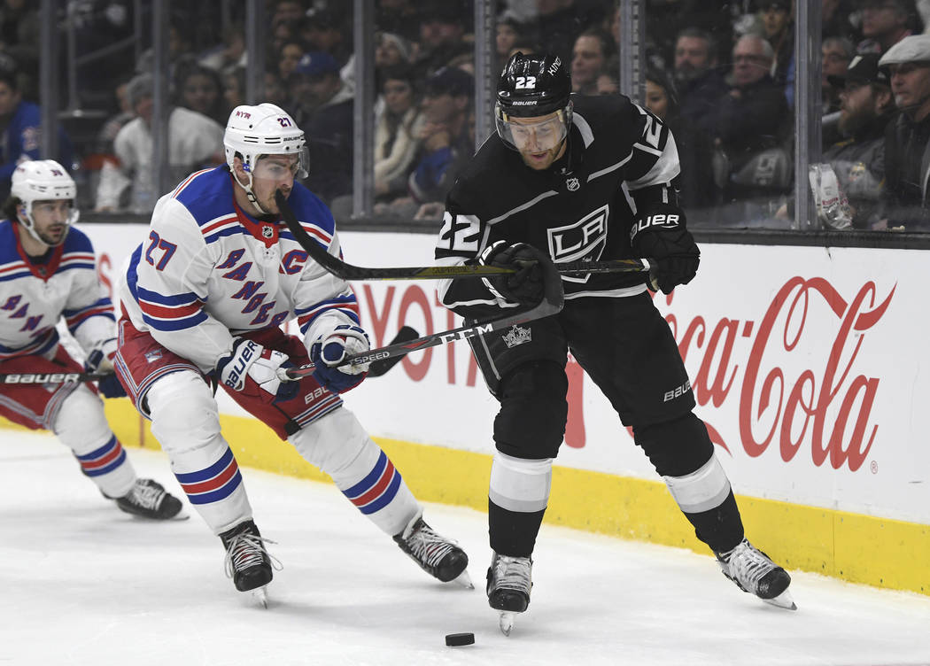New York Rangers defenseman Ryan McDonagh (27) and Los Angeles Kings center Trevor Lewis (22) chase the puck during an NHL hockey game, Sunday, Jan. 21, 2018, in Los Angeles. (AP Photo/Michael Owe ...