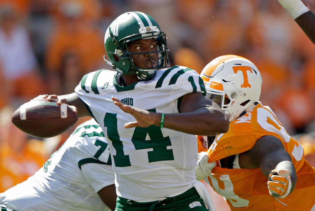 Ohio quarterback Greg Windham (14) throws to a receiver in the second half of an NCAA college football game as he's pressured by Tennessee defensive lineman Kahlil McKenzie (99) Saturday, Sept. 17 ...