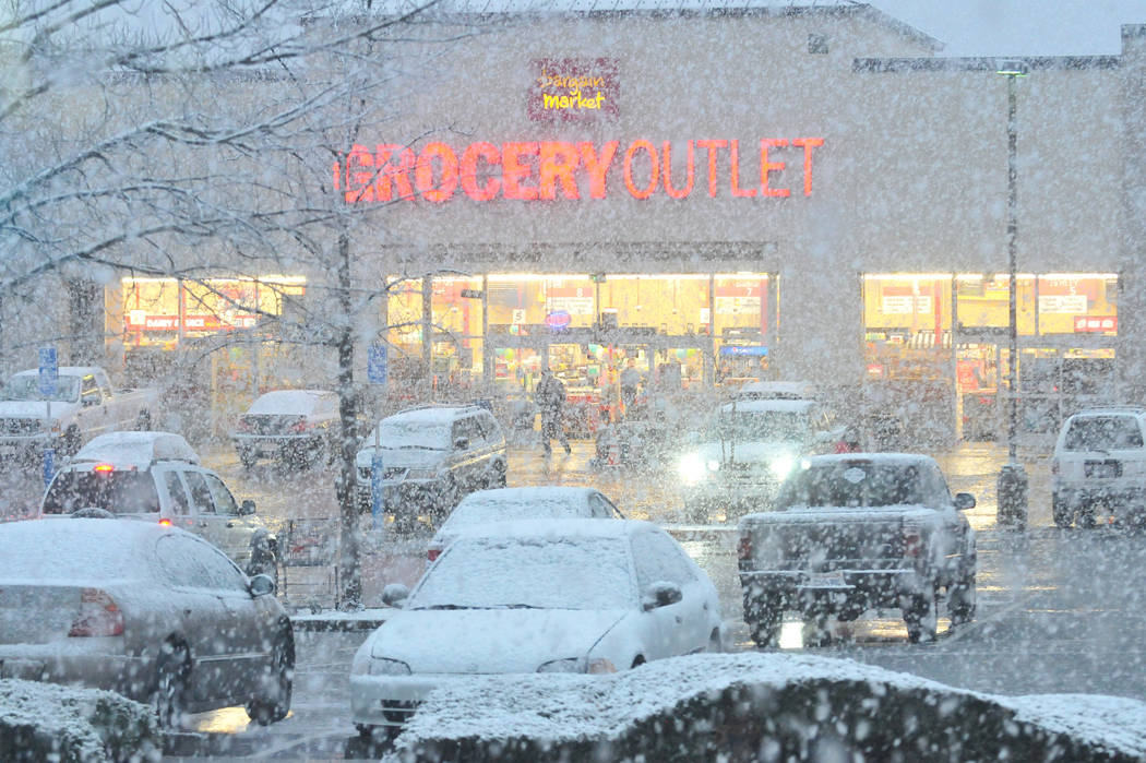 Shoppers navigate the snowy Grocery Outlet parking lot in Glenbrook Basin, Friday, March 2, 2018, in Grass Valley, Calif. (Elias Funez/The Union via AP)