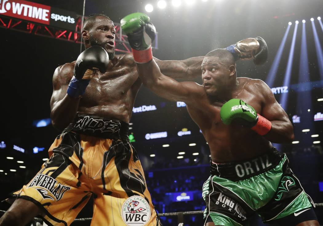 Deontay Wilder, left, and Luis Ortiz trade punches during the third round of the WBC heavyweight championship bout Saturday, March 3, 2018, in New York. Wilder stopped Ortiz in the 10th round. (AP ...