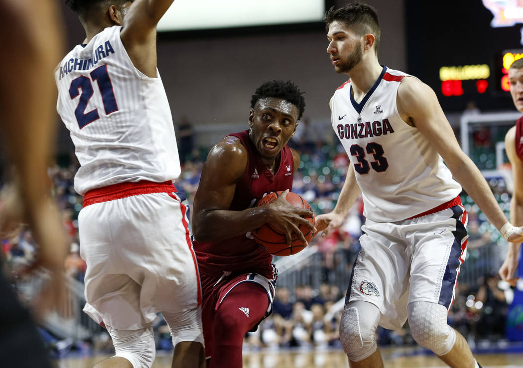 Loyola Marymount Lions guard James Batemon, center, looks for an opening through Gonzaga forward Rui Hachimura (21) and forward Killian Tillie (33) during the West Coast Conference Basketball Tour ...