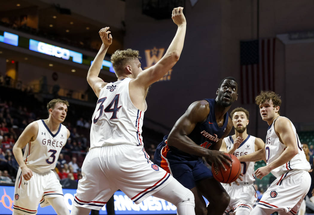 Pepperdine Waves forward Matthew Atewe (41) looks to shoot as St. Mary's Gaels center Jock Landale (34) defends during the West Coast Conference Basketball Tournament quarterfinals at the Orleans  ...