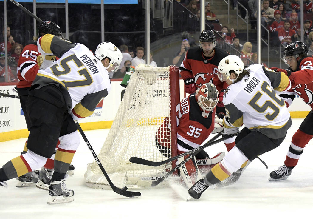 New Jersey Devils goaltender Cory Schneider (35) guards the net as Vegas Golden Knights' David Perron (57) and Erik Haula (56) apply pressure during the first period of an NHL hockey game Sunday,  ...