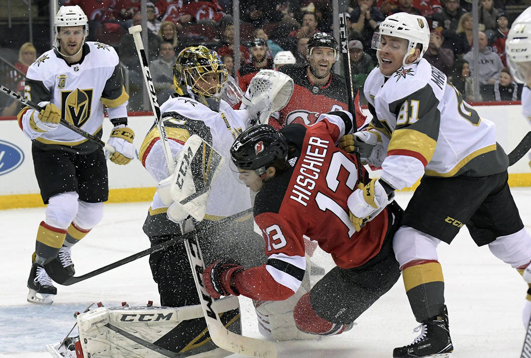 New Jersey Devils center Nico Hischier (13) is checked by Vegas Golden Knights center Jonathan Marchessault (81) into Golden Knights goaltender Marc-Andre Fleury (29) during the second period of a ...