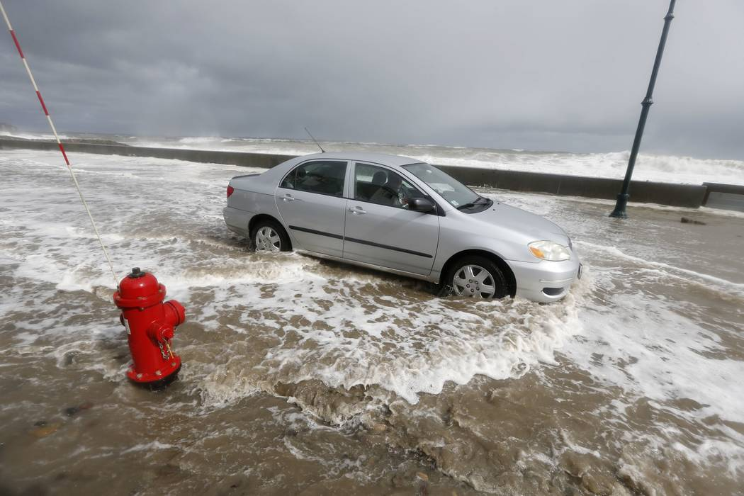A car drives through flood waters in Winthrop, Mass., Saturday, March 3, 2018, a day after a nor'easter pounded the Atlantic coast with hurricane-force winds and sideways rain and snow, flooding s ...