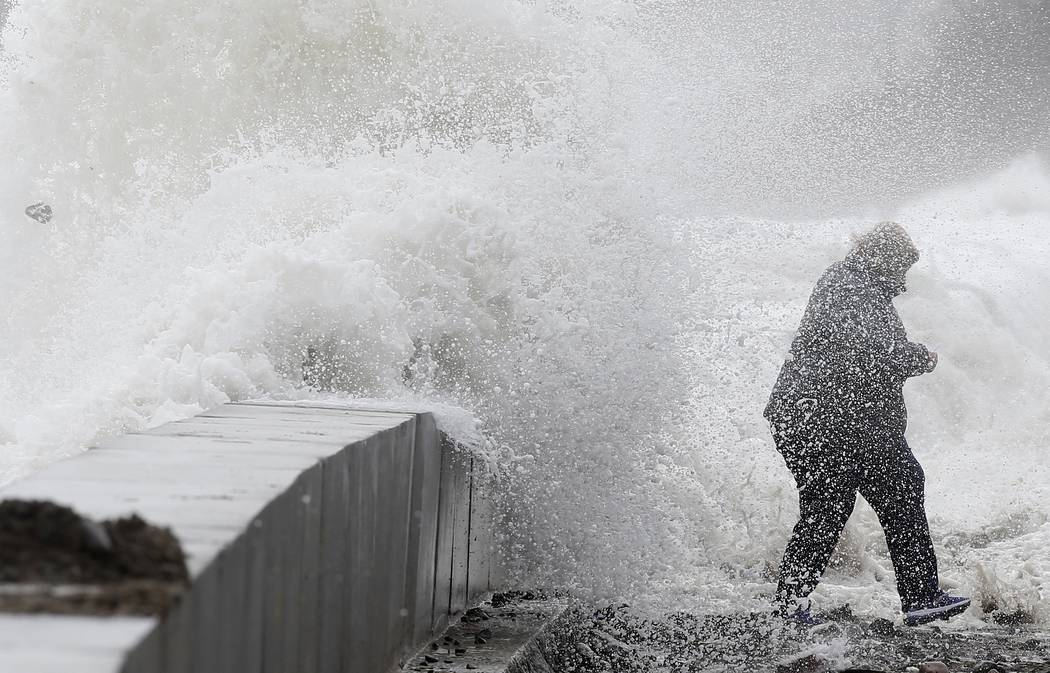 A woman gets caught by a wave as heavy seas continue to come ashore in Winthrop, Mass., Saturday, March 3, 2018, a day after a nor'easter pounded the Atlantic coast with hurricane-force winds and  ...