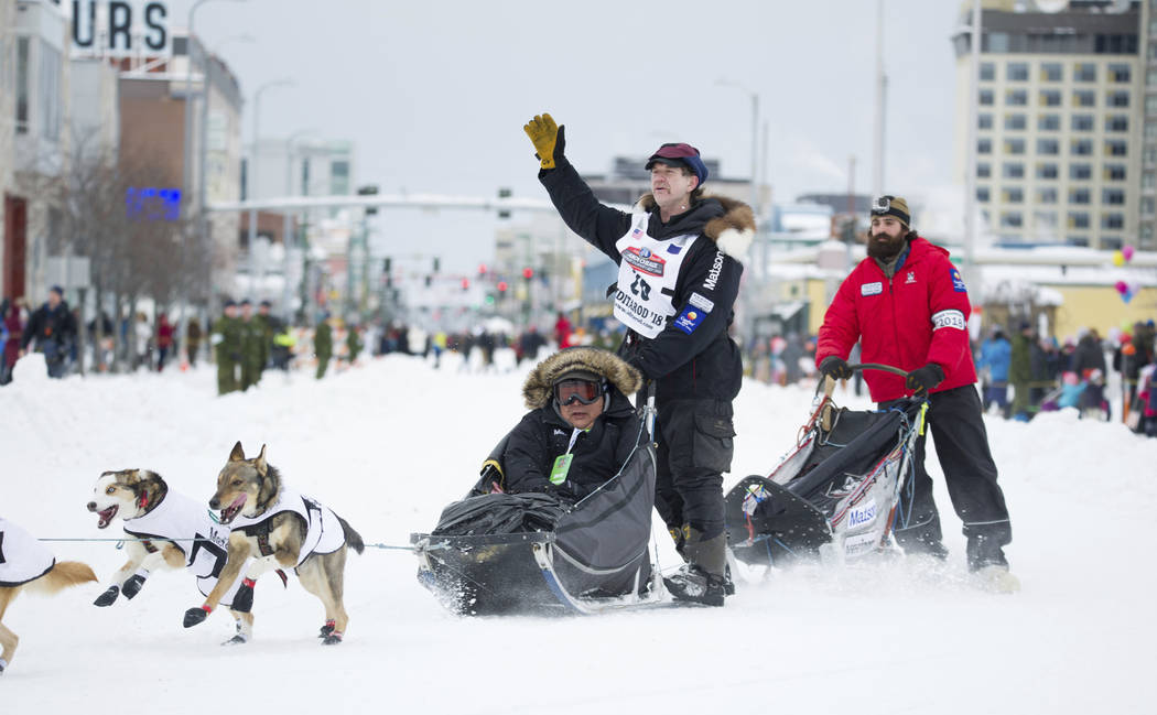 Iditarod musher Allen Moore waves to the crowd during the ceremonial start of the Iditarod Trail Sled Dog Race, Saturday, March 3, 2018, in Anchorage, Alaska. Moore has just won the Yukon Quest, a ...