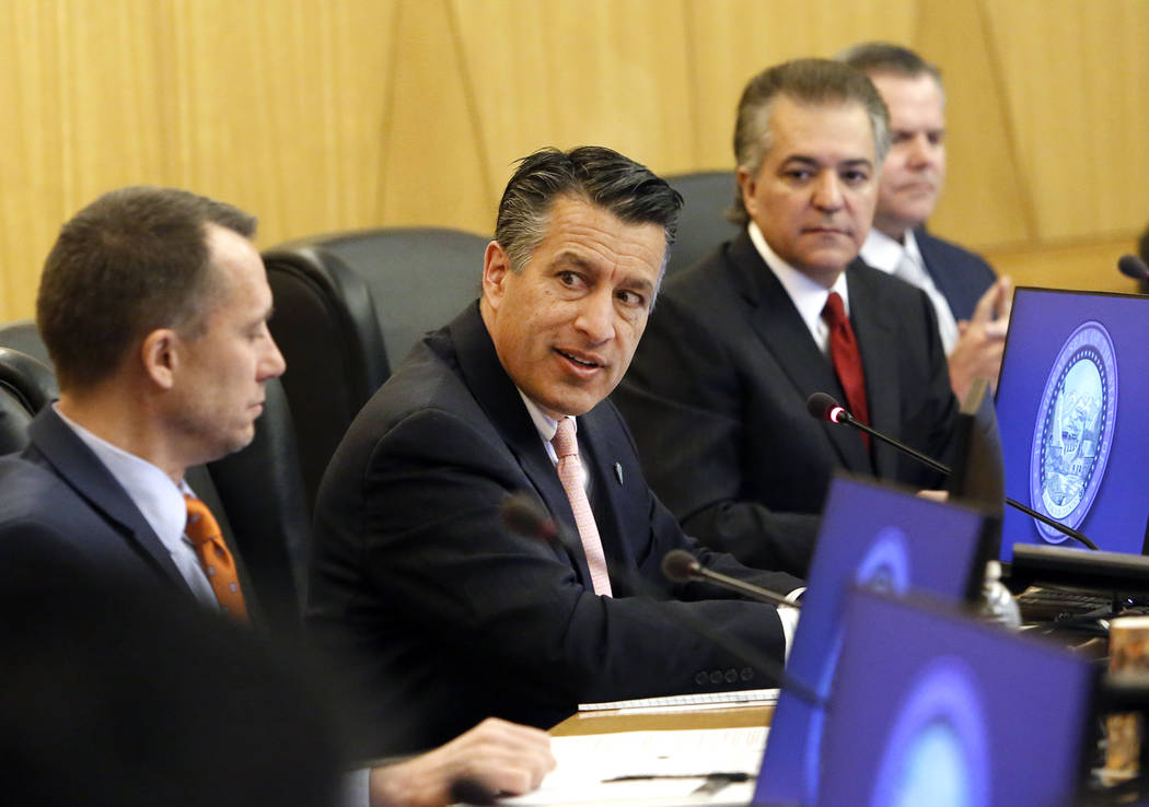 Gov. Brian Sandoval, center, speaks as Gaming Control Board Chairman, A.G. Burnett, left, and Gaming Commission Chairman, Tony Alamo, look on during the Gaming Policy Committee discusses marijuana ...