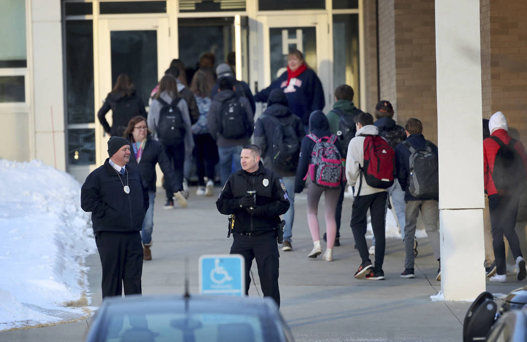 Police officers stand guard on Feb. 22 as Orono High School students arrive for school, one day after a threat was posted, causing the school to go on lockdown in Orono, Minn.(David Joles/Star Tri ...