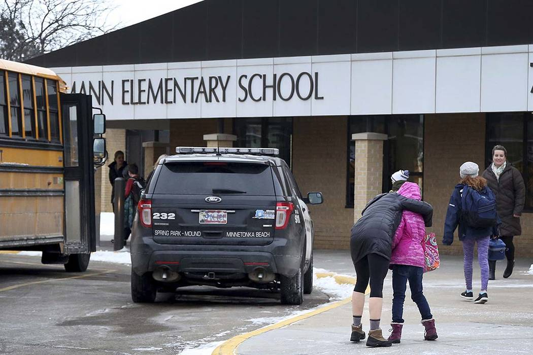 Meghan Stephenson hugs her child before staying goodbye on Feb. 22 outside Orono Schumann Elementary School as a police officer stands nearby as students arrive for the day after a threat was post ...
