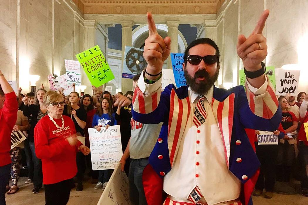 Parry Casto, a fifth grade teacher at the Explorer Academy in Huntington, W.Va., dressed in an Uncle Sam costume leads hundreds of teachers in chants outside the state Senate chambers on March 1 a ...