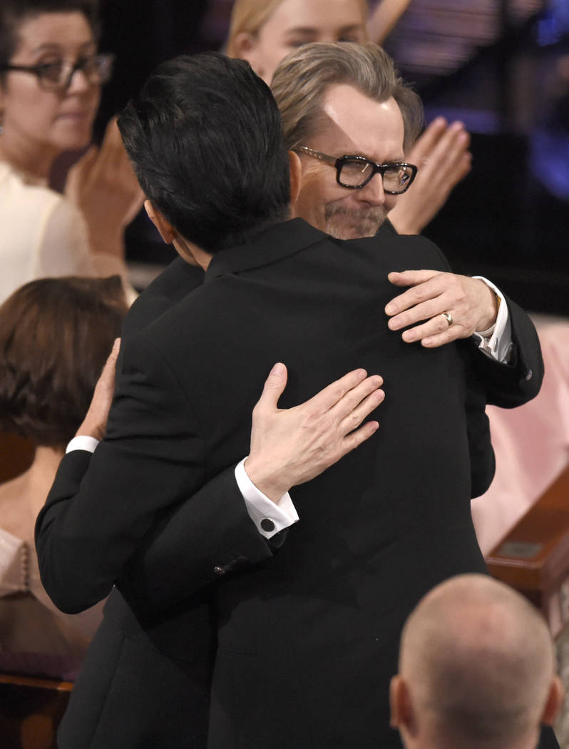 """Gary Oldman congratulates Kazuhiro Tsuji in the audience as he wins the award for best makeup and hairstyling for """"Darkest Hour"""" at the Oscars on Sunday, March 4, 2018, at the Dolby Thea ..."""