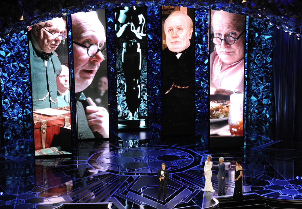 """Gary Oldman accepts the award for best performance by an actor in a leading role for """"Darkest Hour"""" as Helen Mirren from right and Jane Fonda look on at the Oscars on Sunday, March 4, 20 ..."""