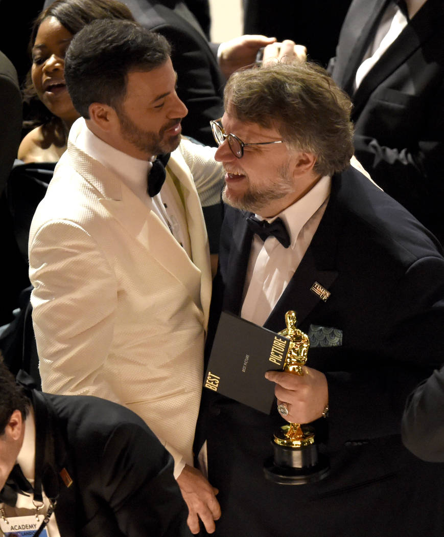 """Jimmy Kimmel, left, congratulates Guillermo del Toro in the audience after winning the award for best picture for """"The Shape of Water"""" at the Oscars on Sunday, March 4, 2018, at the Dolb ..."""