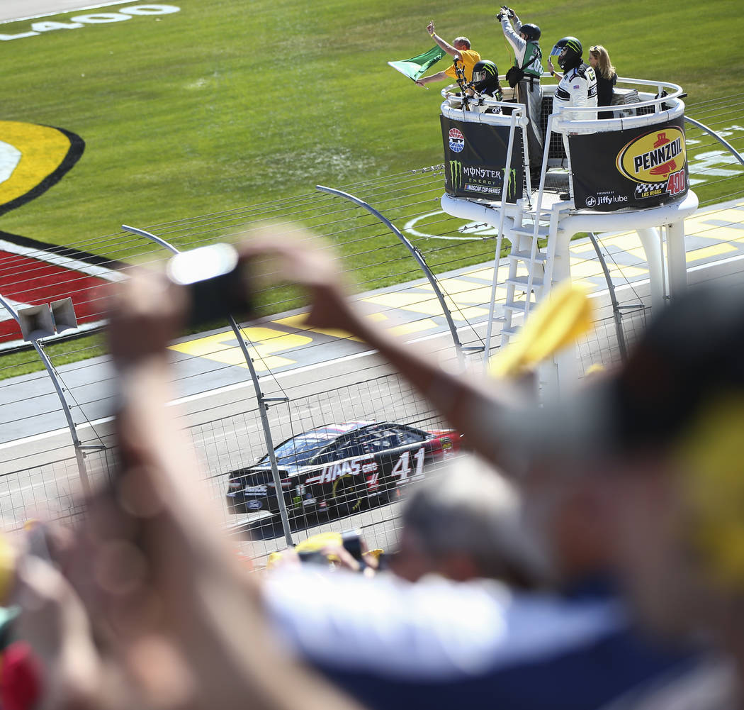 The green flag is waved at the start of the Monster Energy NASCAR Cup Series Pennzoil 400 auto race at the Las Vegas Motor Speedway in Las Vegas on Sunday, March 4, 2018, as a fun takes a photo of ...
