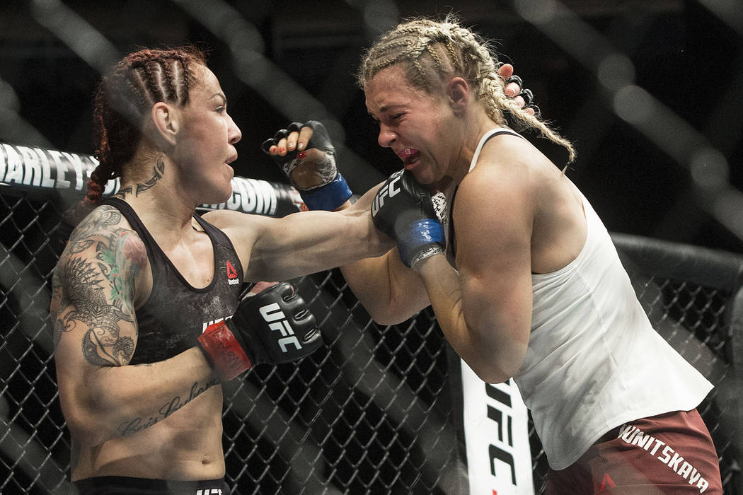 "Cris ""Cyborg"" Justino, left, connects with a left hook against Yana Kunitskaya during their featherweight championship mixed martial arts bout at UFC 222 on Saturday, March 3, 2018, in L ..."