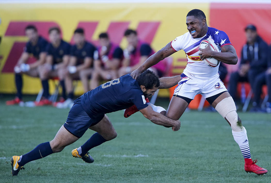 Kevon Aaron Williams, right, deflects a tackle from Argentina's Gaston Revol (8) during the HSBC USA Sevens rugby tournament Cup Final's in Las Vegas on Sunday, March 4, 2018. Richard Brian Las Ve ...