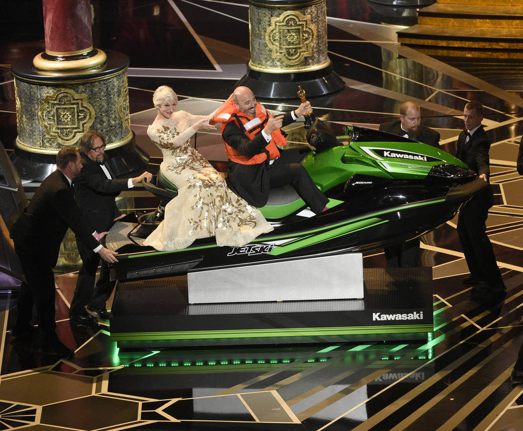 "Helen Mirren, left, accompanies Mark Bridges, winner for the award for best costume design for ""Phantom Thread,"" as he wins a jet ski for having the shortest acceptance speech at the Osc ..."