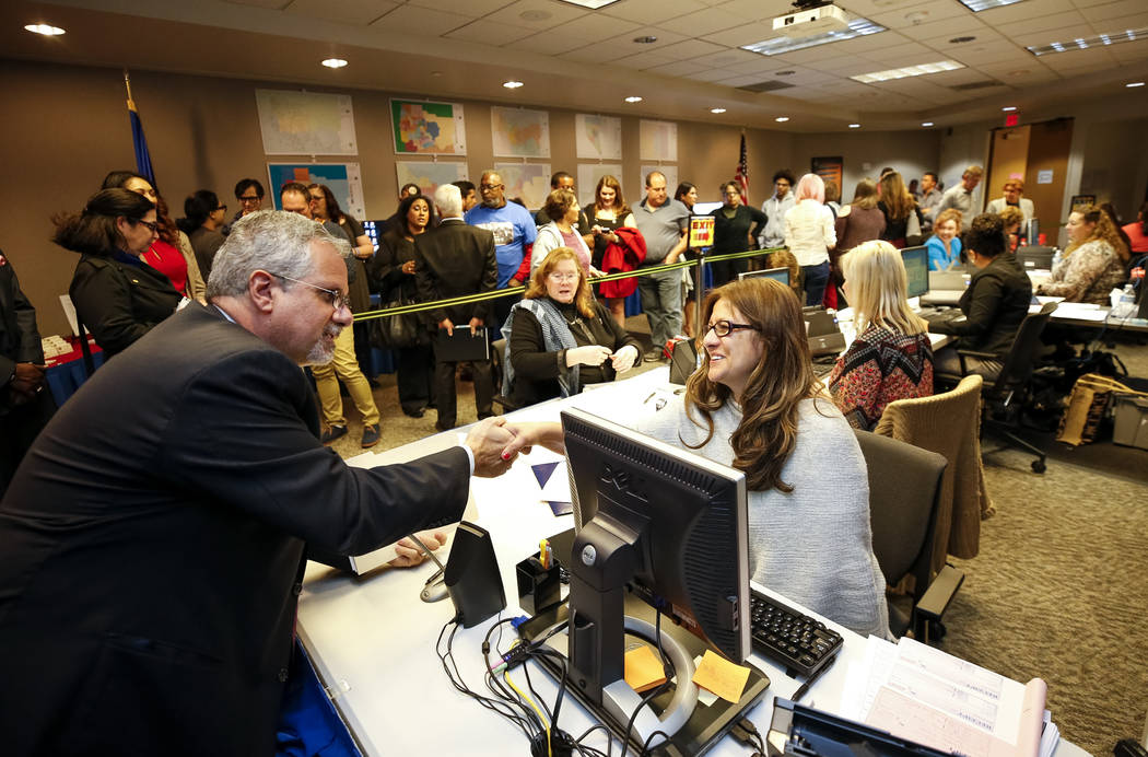 Ozzie Fumo, left, shakes hands with office specialist Magdelena Lopez after he filed to run for State Assembly, District 21 during the first day of candidate filing at the Clark County Government  ...