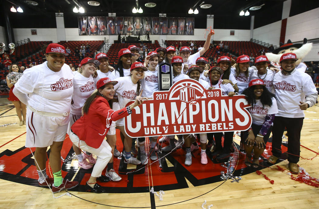 UNLV Lady Rebels players celebrate their regular season Mountain West championship win with their coach Kathy Olivier, red jacket, after defeating Utah State at the Cox Pavilion in Las Vegas on Fr ...