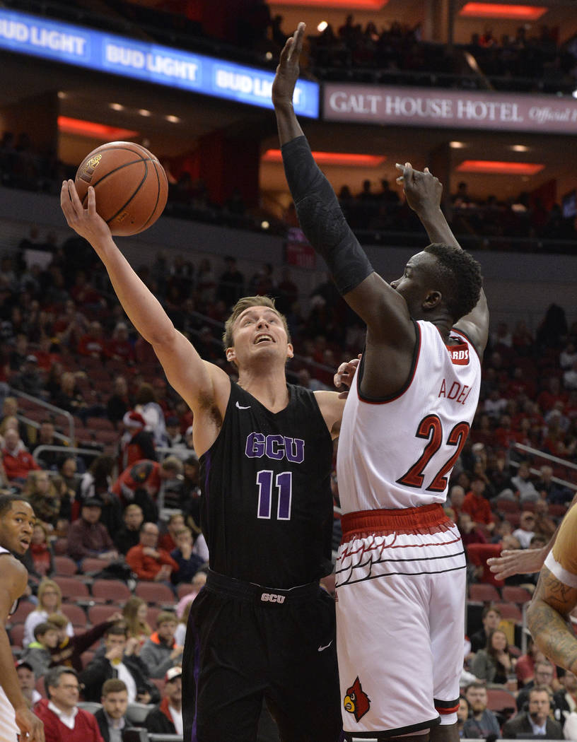 Grand Canyon guard Casey Benson (11) attempts a shot over the defense of Louisville forward Deng Adel (22) during the first half of an NCAA college basketball game, Saturday, Dec. 23, 2017, in Lou ...
