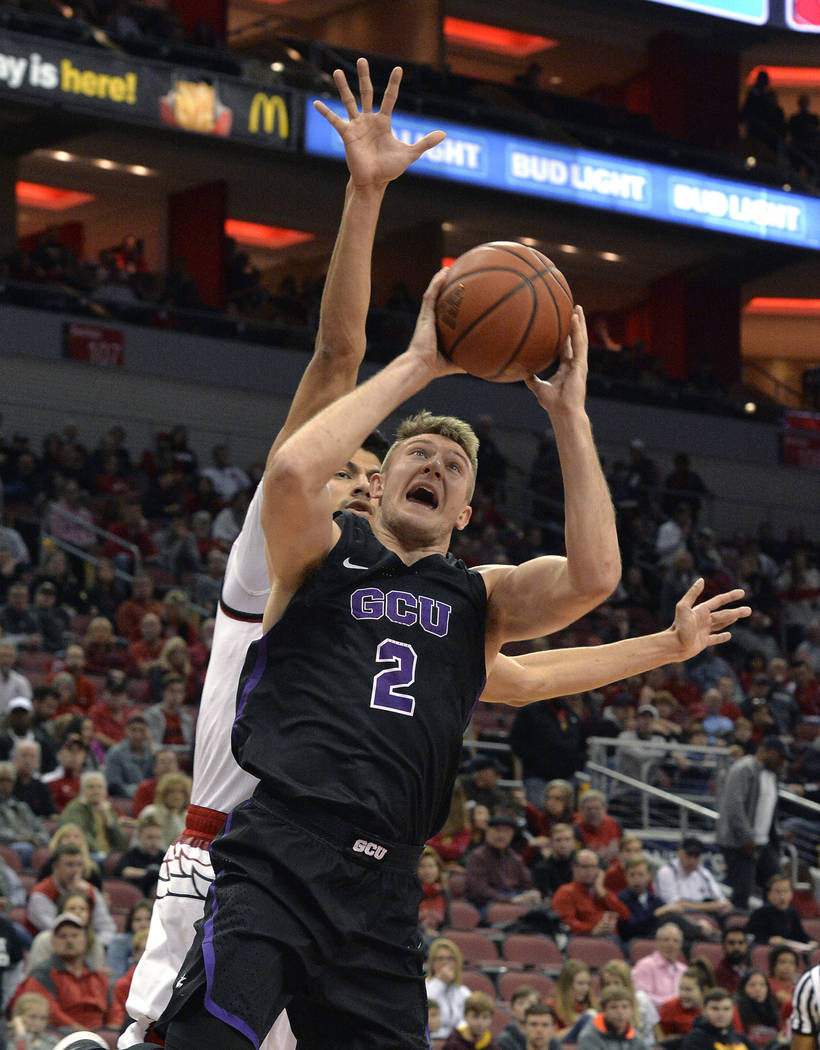 Grand Canyon guard Joshua Braun (2) goes in for a layup around the defense of Louisville forward Anas Mahmoud (14) during the first half of an NCAA college basketball game, Saturday, Dec. 23, 2017 ...