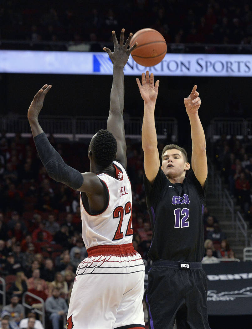 Louisville guard Jacob Redding (12) shoots over the reach of Louisville forward Deng Adel (22) during the first half of an NCAA college basketball game, Saturday, Dec. 23, 2017, in Louisville, Ky. ...