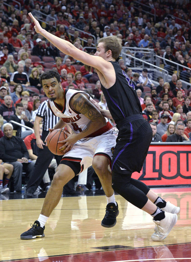 Louisville guard Quentin Snider (4) looks for help from the defensive pressure of Grand Canyon guard Casey Benson (11) during the second half of an NCAA college basketball game, Saturday, Dec. 23, ...