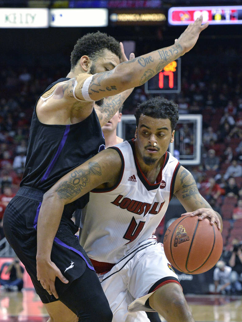 Louisville guard Quentin Snider (4) attempts to drive around the defense of Grand Canyon forward Keonta Vernan (24) during the second half of an NCAA college basketball game, Saturday, Dec. 23, 20 ...