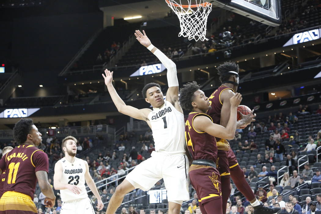 Colorado Buffaloes' Tyler Bey (1) goes for a rebound against Arizona State's Kimani Lawrence (14) and De'Quon Lake (35) during an NCAA college basketball game in the first round of the Pac-12 tour ...