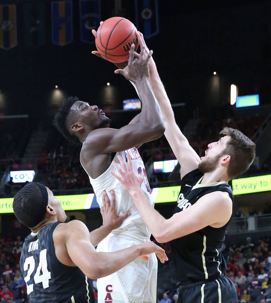 Arizona Wildcats' Deandre Ayton, center, shoots over Colorado Buffaloes' George King (24) and Lucas Siewert (23) during an NCAA college basketball game in the quarter final of the Pac-12 tournamen ...