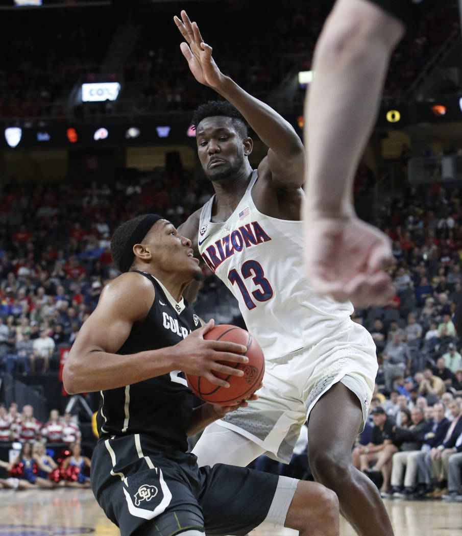 Arizona Wildcats' Deandre Ayton (13) defends Colorado Buffaloes' George King (24) during an NCAA college basketball game in the quarter final of the Pac-12 tournament on Thursday, March 8, 2018, i ...
