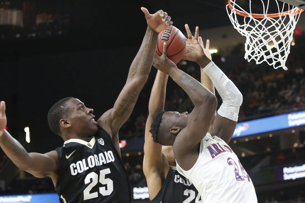 Colorado Buffaloes' McKinley Wright IV (25) and George King (24) defend Arizona Wildcats' Emmanuel Akot (24) during an NCAA college basketball game in the quarter final of the Pac-12 tournament on ...