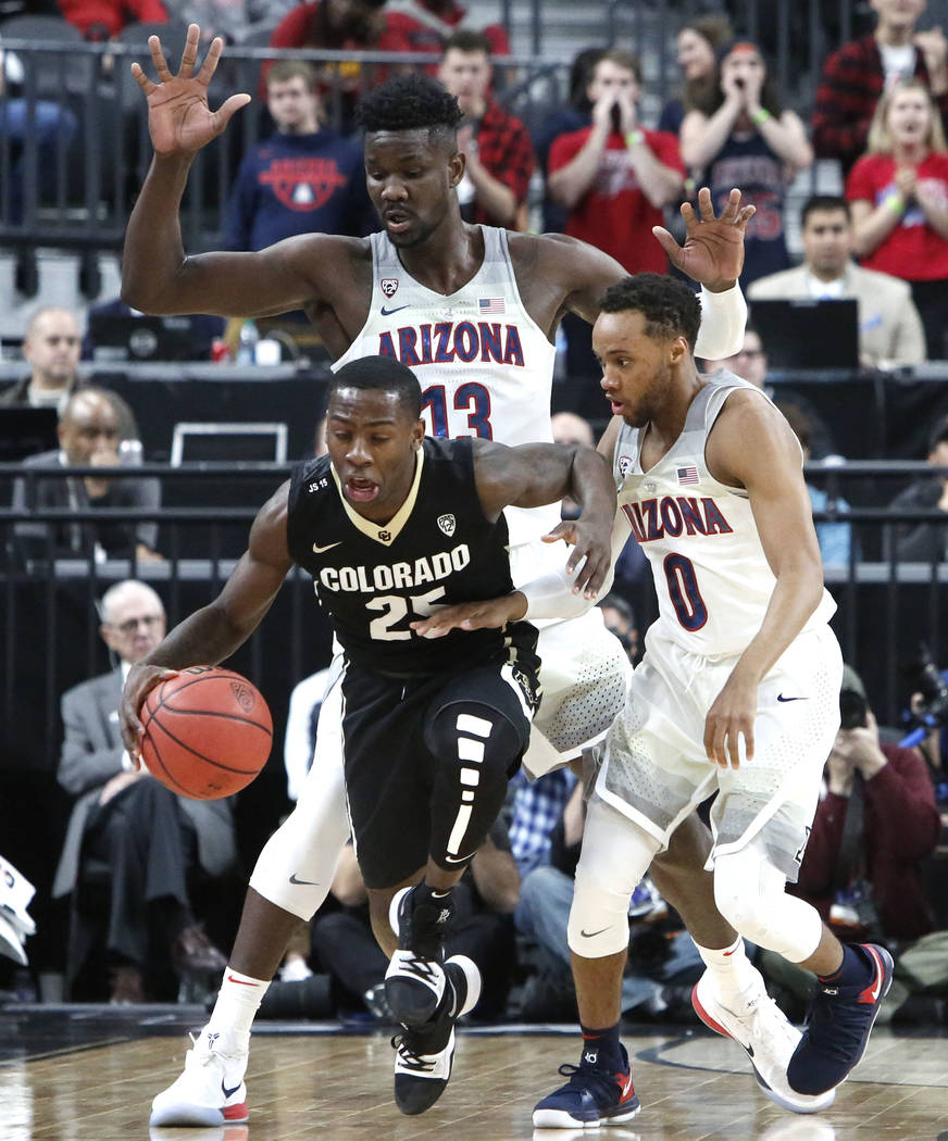 Colorado Buffaloes' McKinley Wright IV (25) drives past Arizona Wildcats' Deandre Ayton (13) and Parker Jackson-Cartwright (0) during an NCAA college basketball game in the quarter final of the Pa ...