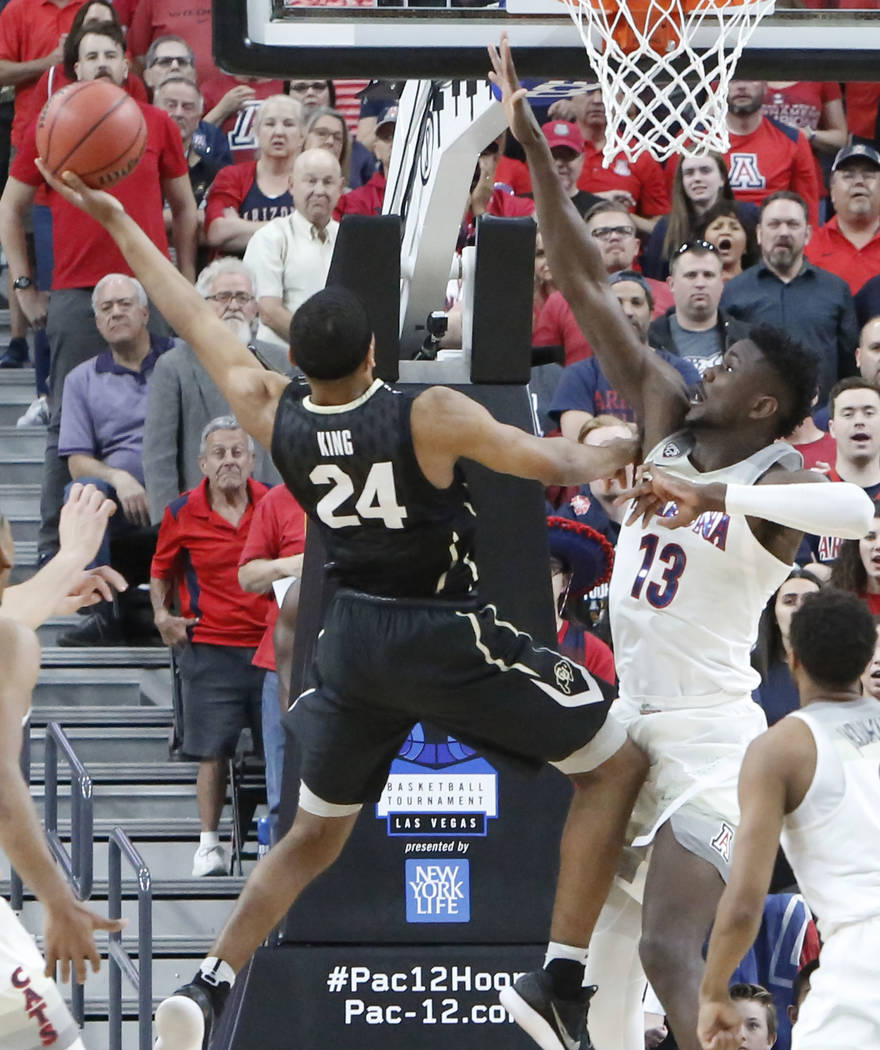 Colorado Buffaloes' George King (24) tries to shoot over Arizona Wildcats' Deandre Ayton (13) during an NCAA college basketball game in the quarter final of the Pac-12 tournament on Thursday, Marc ...