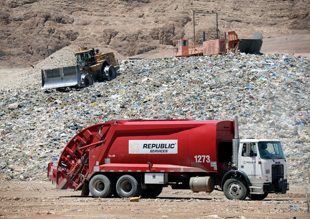 A trash truck arrives as workers use heavy equipment to push the rubbish at the Apex Regional Landfill on Thursday, May 17, 2012.  Republic Services has partnered with Energenic to build the new A ...