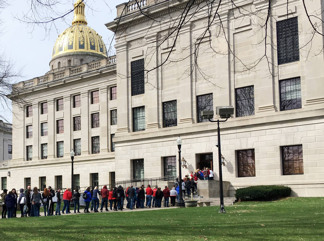 Striking West Virginia teachers line up to enter the state Capitol on Monday, March 5, 2018, in Charleston, W.Va. Teachers are waiting for state lawmakers to agree on a pay raise, and state House  ...