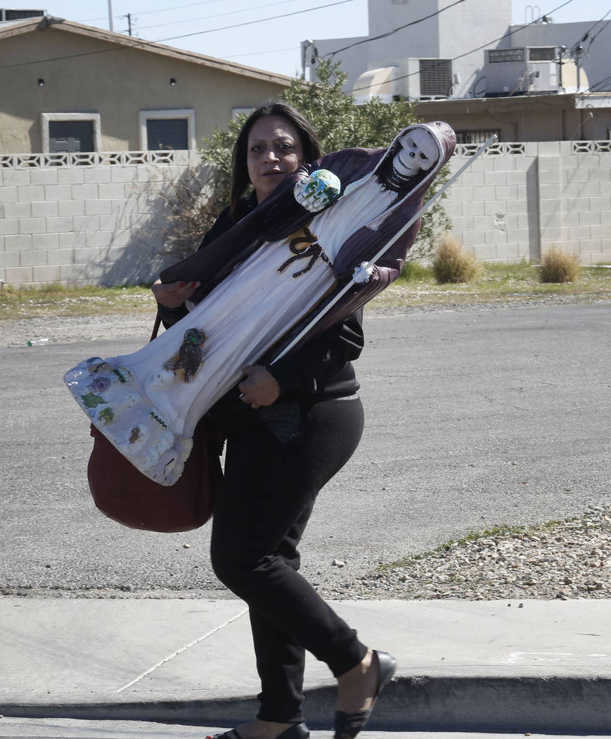 Veronica Flores carries her statue after being evicted from Las Haciendas Apartments at 2504 Las Vegas Blvd. North on Monday, March 5, 2018. Twenty-five families were evicted from their apartments ...