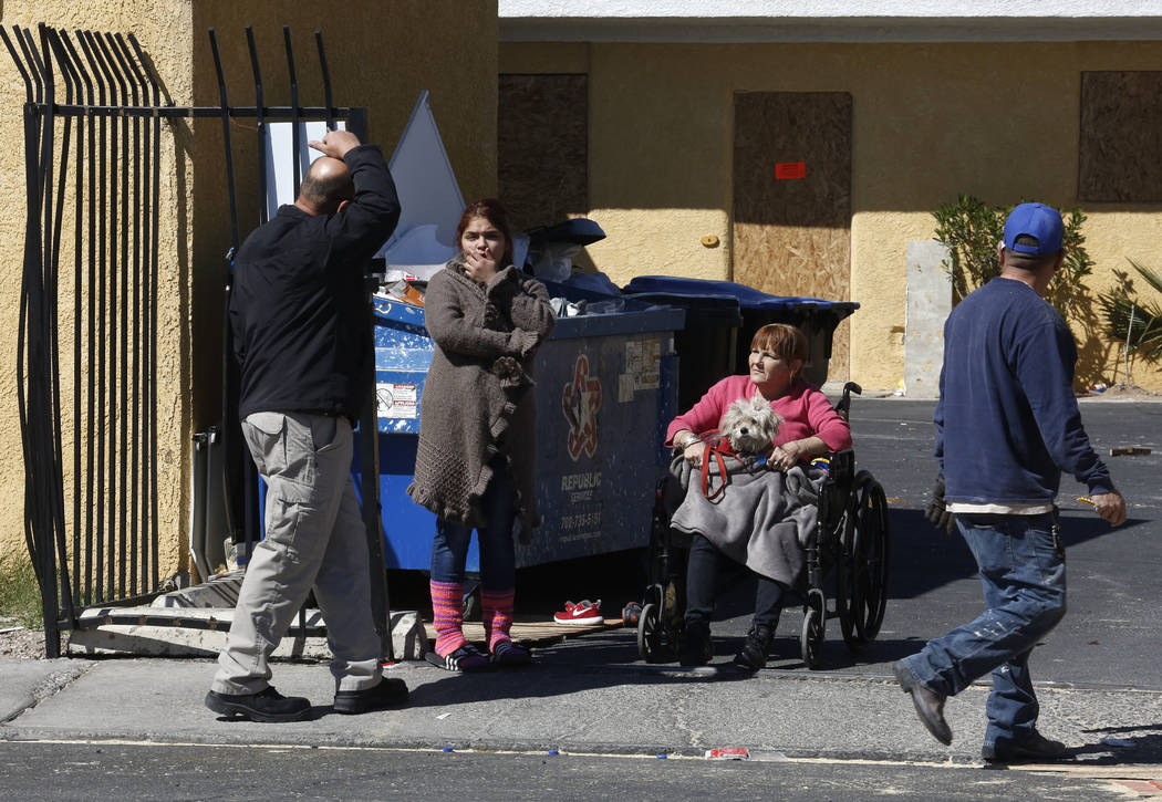 Tenants, including Paloma Castrejon, center, and her dog Princess gather outside their boarded up apartment on Monday, March 5, 2018 at Las Haciendas Apartments at 2504 Las Vegas Blvd., North. Twe ...
