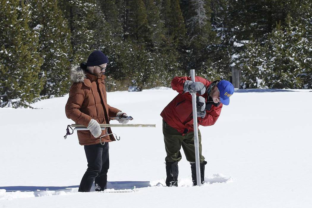 Frank Gehrke, chief of the California Cooperative Snow Surveys Program, for the Department of Water Resources, right, plunges the snow survey tube into the snow to check the depth of the snowpack  ...