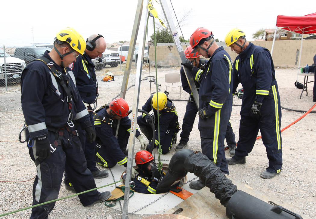Members of the Clark County Fire Department Heavy Rescue program lower a fighter into a manhole above a Regional Flood Control underground waterway near West Russel Road and South Tenaya Way in La ...
