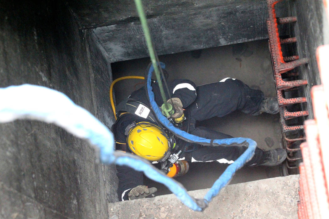 A member of the Clark County Fire Department Heavy Rescue program gets lowered into a manhole above a Regional Flood Control underground waterway near West Russel Road and South Tenaya Way in Las  ...