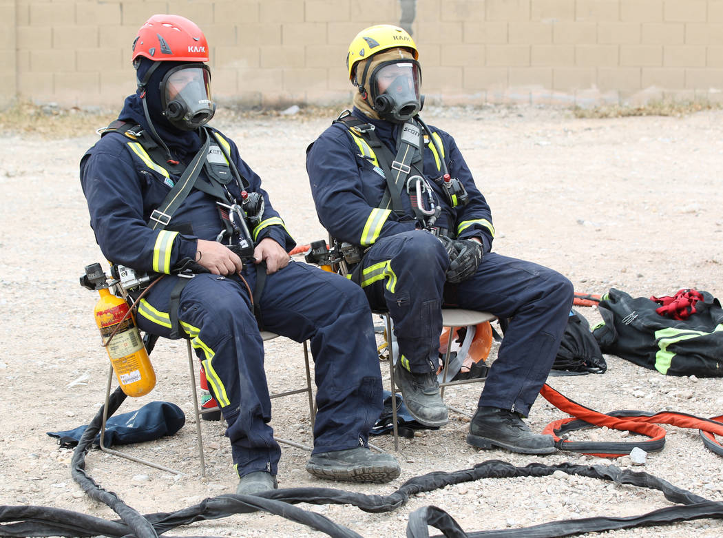 Members of the Clark County Fire Department Heavy Rescue program wait to be lowered into a manhole above a Regional Flood Control underground waterway near West Russel Road and South Tenaya Way in ...