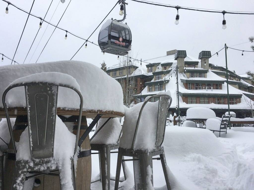 In this photo provided by the Heavenly Mountain Resort, fresh snow covers most of a table and chairs Friday, March 2, 2018, in South Lake Tahoe, Calif. A blizzard warning was in effect for parts o ...