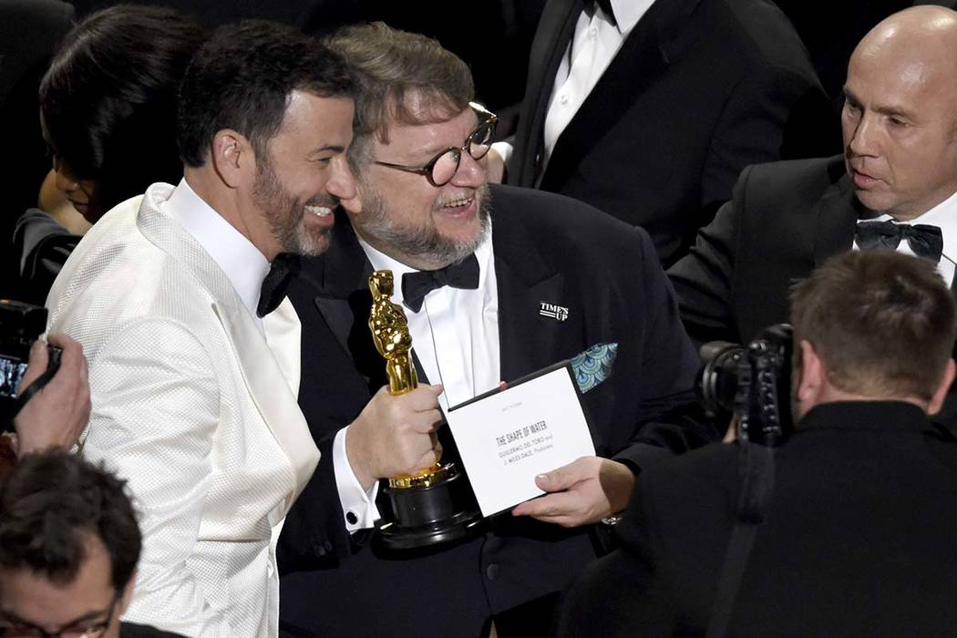 "Jimmy Kimmel, left, congratulates Guillermo del Toro in the audience after winning the award for best picture for ""The Shape of Water"" at the Oscars on Sunday, March 4, 2018, at the Dolb ..."