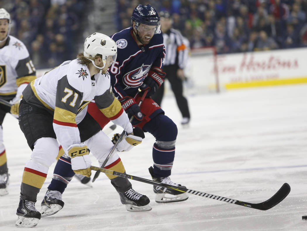 Las Vegas Golden Knights' William Karlsson, left, of Sweden, and Columbus Blue Jackets' Thomas Vanek, of Austria, chase the puck during the first period of an NHL hockey game Tuesday, March 6, 201 ...